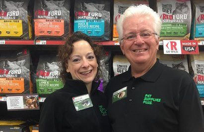 a father and daughter franchise pair are standing in the aisle of the store