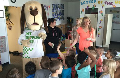 The PSP mascott is interacting with kids in a classroom
