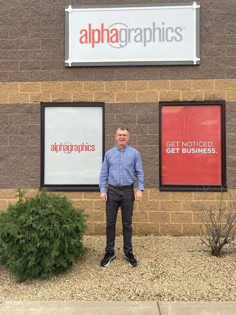 man standing in front of AlphaGraphics storefront