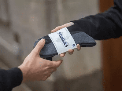 Bombas socks being handed to someone