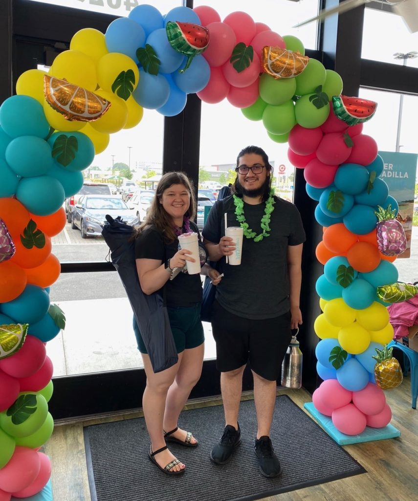 Guest at Grand Opening with smoothies under a balloon arch
