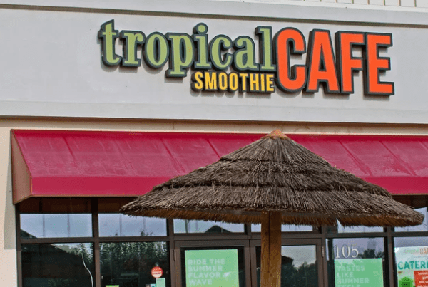 Exterior of Tropical smoothie location with umbrella in front.