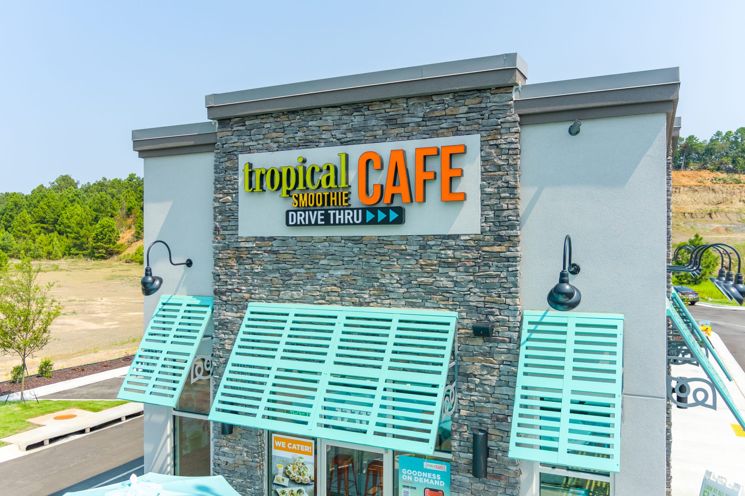 Exterior of Tropical Smoothie Cafe building with teal awnings and logo
