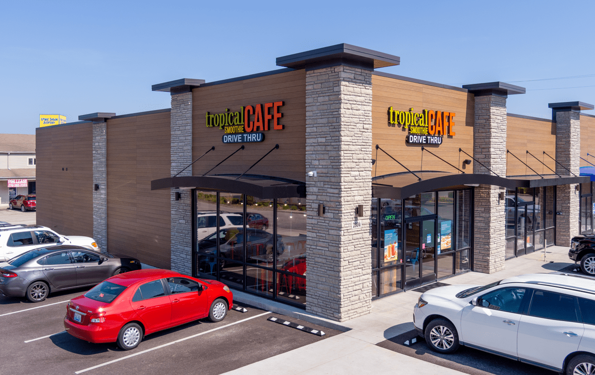 exterior of tropical smoothie cafe location on a corner with cars parked out front