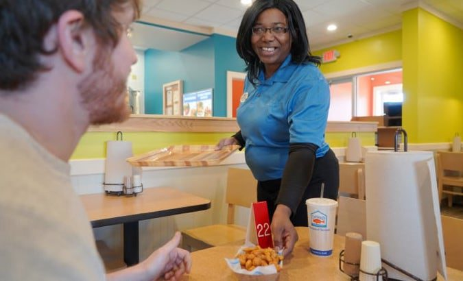 Captain D's employee delivering order to a table